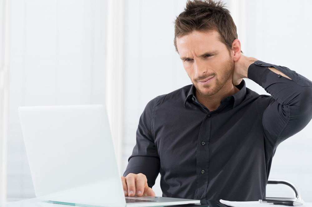 Man holding neck from chiropractor neck pain